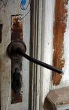 Gammalt rostigt dörrhandtag för tappning på en åldrig vit dörr royaltyfri foto