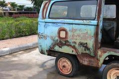 Gammalt rostigt för bil med det plana gummihjulet av övergett Royaltyfri Fotografi