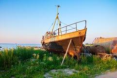 Gammalt rostigt fartyg på seashoren med grönt gräs Arkivbilder
