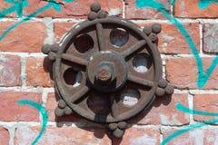 Gammalt rostigt järnstyrninghjul med en modell som hänger på en vägg för röd tegelsten arkivfoto