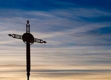 Gammalt rostigt kors, över härlig aftonhimmel Arkivbilder