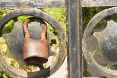 Gammalt rostigt lås på en metallport in i trädgården Lås på järnporten Symbolinspärrning och slaveri Egenskapssäkerhetskedja Arkivbilder