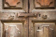 Gammalt rostigt låser tätt upp på en forntida trädörr med metallhandtag Arkivfoto