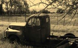 Gammalt rostigt lastbilsammanträde för tappning i ett fält Royaltyfri Foto