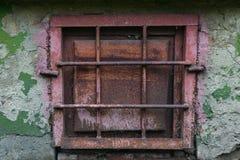 gammalt rostigt metallfönster med gallret på en skalningsvägg royaltyfri fotografi