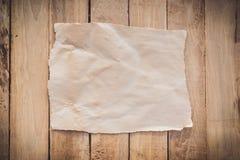 Gammalt sönderrivet papper på wood bakgrund royaltyfria foton
