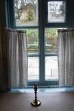 Gammalt skrivbord med en stearinljus mot fönstret härlig tappning för bakgrund Arkivbild
