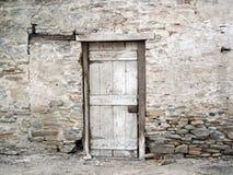 Gammalt smula vaggar väggen med en dörr royaltyfri fotografi