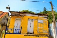 Gammalt, snedvridit gult trähus Puerto Plata dominikan Republ arkivbild
