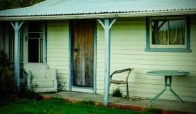 Gammalt sommarhus med gamla stolar på verandan Arkivfoto