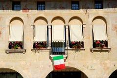 Gammalt stadshus med blommor i Oderzo i landskapet av Treviso i Venetoen (Italien) arkivfoto