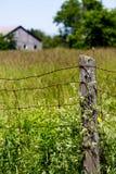Gammalt staket i ett fält med ett wood hus arkivbilder