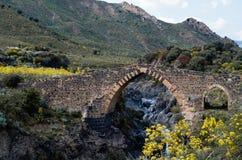 Gammalt stena bron ?ver floden i bergen royaltyfria foton