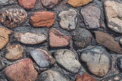 Gammalt stena väggen av blandade stenar och tegelstenar arkivbild