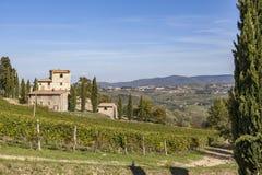 Gammalt stenhus på en kulle med vingårdar i Chianti i Tuscany I royaltyfri fotografi