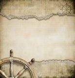 Gammalt styrninghjul och sönderriven nautisk översikt Arkivfoto
