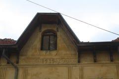 Gammalt tak av ett gult hus med någon romersk inskrift Royaltyfri Foto