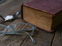 Gammalt tappningbokRyss-tysk ordbok, exponeringsglas & armbandsur Royaltyfri Fotografi