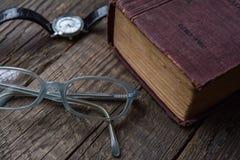 Gammalt tappningbokRyss-tysk ordbok, exponeringsglas & armbandsur Arkivbilder