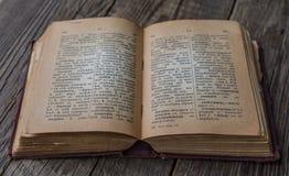 Gammalt tappningbokRyss-tysk ordbok, exponeringsglas & armbandsur Royaltyfri Bild