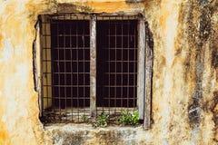 Gammalt tappningfönster av för modedesign för hus den gamla klassikern på gul lantlig målad betongväggbakgrund royaltyfri fotografi