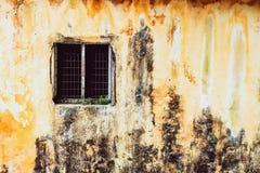 Gammalt tappningfönster av för modedesign för hus den gamla klassikern på gul lantlig målad betongväggbakgrund royaltyfri foto