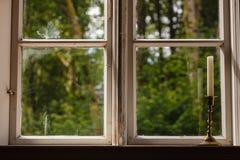 Gammalt tappningfönster och vertikal stearinljus i ljusstake Arkivfoto