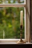 Gammalt tappningfönster och vertikal stearinljus i ljusstake Arkivbild