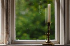 Gammalt tappningfönster och vertikal stearinljus i ljusstake Arkivfoton