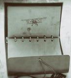 Gammalt tappningfoto av läderanteckningsboken med pennbilden av ett flygplan Arkivfoton