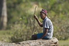 Gammalt Tharu mansammanträde på en journal royaltyfri fotografi