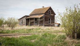 Gammalt träövergett hus med en luta till Arkivfoto