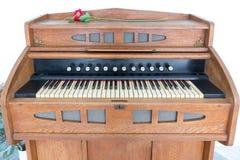 Gammalt träbruntpiano med rosen som överst förläggas royaltyfri foto