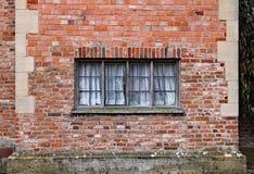 Gammalt träfönster i en riden ut tegelstenvägg i en gammal mangårdsbyggnad royaltyfri foto