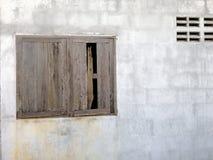 Gammalt träfönster på cementtegelstenväggen arkivbilder