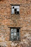 Gammalt träfönster två på den röda bruna tegelstenväggen, textur, backgro Arkivfoton