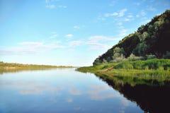 gammalt träfartyg på flodbanken mot bakgrunden av grönt gräs och buskar, reflexioner i vattnet arkivbilder