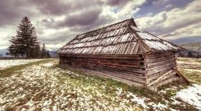 Gammalt trähus i den ljusa himlen Carpathian.Hdr. Arkivfoto