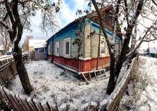Gammalt trähus i en vinter snö-täckt by Staket natur Fotografering för Bildbyråer