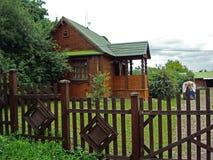 Gammalt trähus med det gröna taket och det bruna staketet royaltyfri fotografi
