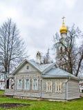 Gammalt trähus på en grön äng med sned fönster Kyrka i bakgrunden Ryskt gammalt hus forntida izba arkivbild