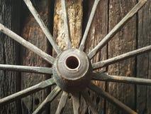 Gammalt trämetallhjul på den gamla träväggbakgrunden Royaltyfri Foto