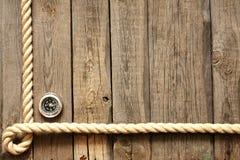 Gammalt träplankor och rep med kompasset Arkivbild