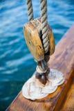 Gammalt träsegelbåtrep som fästas till blocket royaltyfri foto