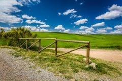 Gammalt trästaket, grusväg och grönt fält Arkivfoto