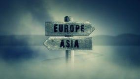 Gammalt trätecken på en mitt av en arg väg med orden Europa eller Asien vektor illustrationer