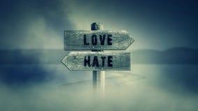 Gammalt trätecken på en mitt av en arg väg med orden förälskelse eller hat vektor illustrationer