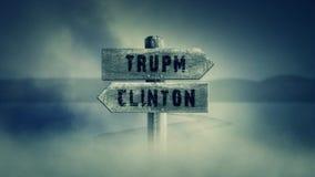 Gammalt trätecken på en mitt av en arg väg med orden trumf eller Clinton royaltyfri illustrationer