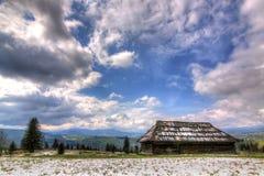 Gammalt trähus i den Carpathian ljusa himlen Arkivfoton