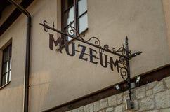Gammalt utsmyckat museumtecken som hänger på fasaden av gammal byggnad royaltyfri fotografi